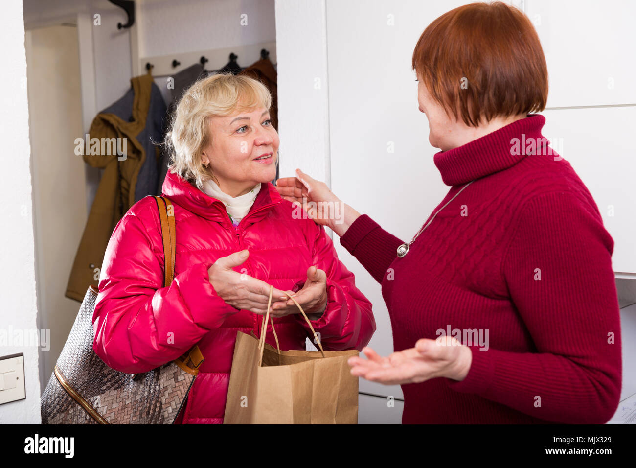Portrait of smiling mature female taking friend woman at home - Stock Image
