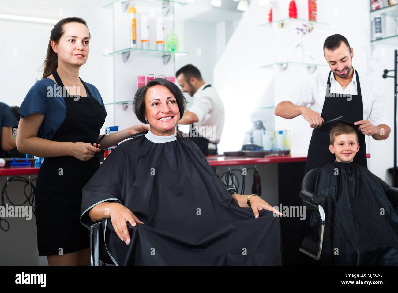 Smiling Woman 40s Getting Haircut By Female Hairdresser In Salon