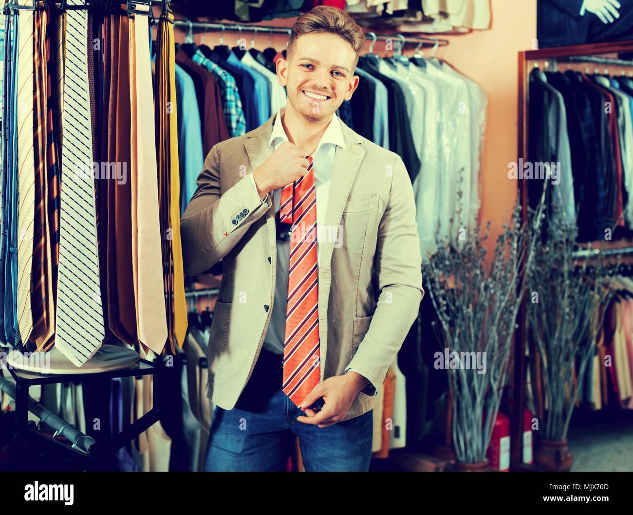 fb2cb275 Young man choosing new suit in men's cloths store Stock Photo ...