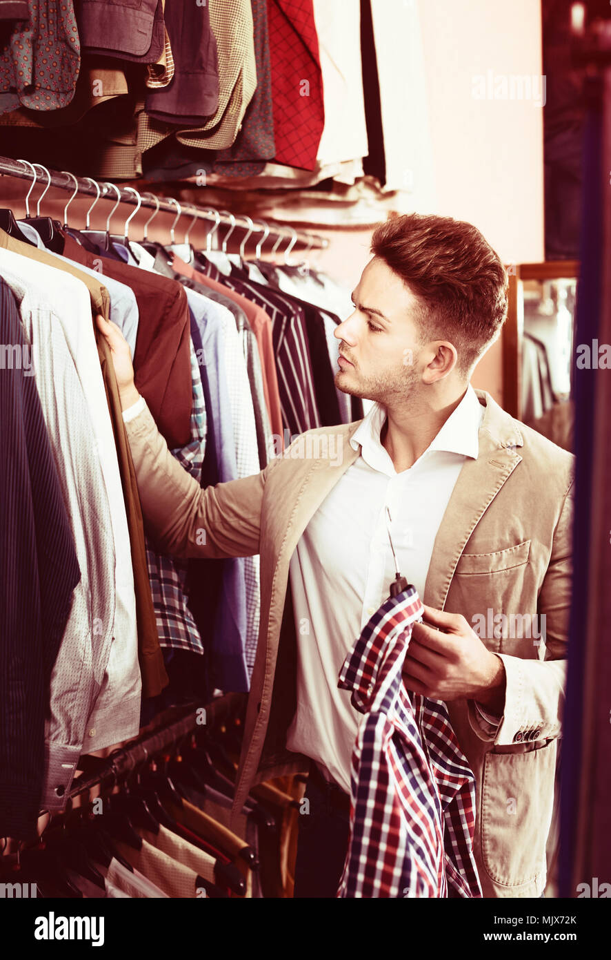 6fc217b8 Positive young man choosing new shirt in men's clothes store Stock ...
