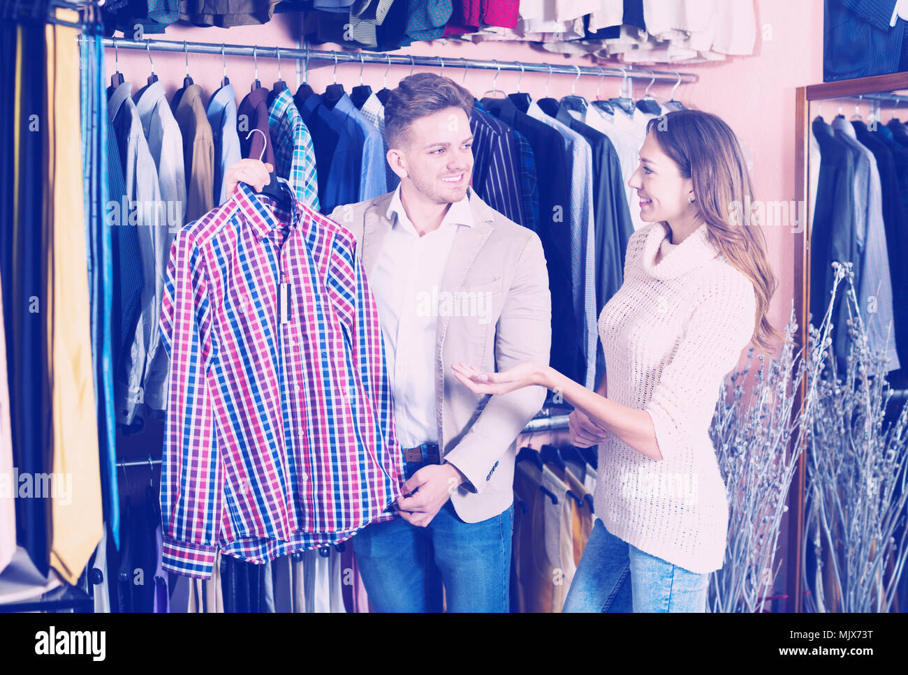 2036cba3f46f Smiling young man and woman examining various shirts in men's clothes shop
