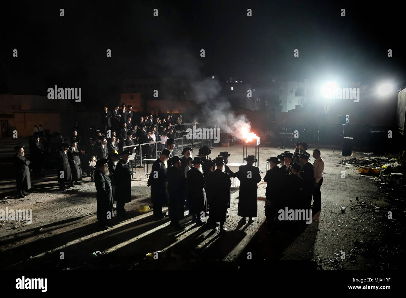 Ultra-Orthodox Jewish men from the Shomrei Emunim Hassidic dynasty dance as they light a giant oil fire in the Geula religious neighborhood during the celebration of Lag BaOmer holiday which marks the celebration, interpreted by some as anniversary of death of Rabbi Shimon bar Yochai, one of Judaism's great sages some 1800 years ago and the day on which he revealed the deepest secrets of kabbalah a landmark text of Jewish mysticism - Stock Image