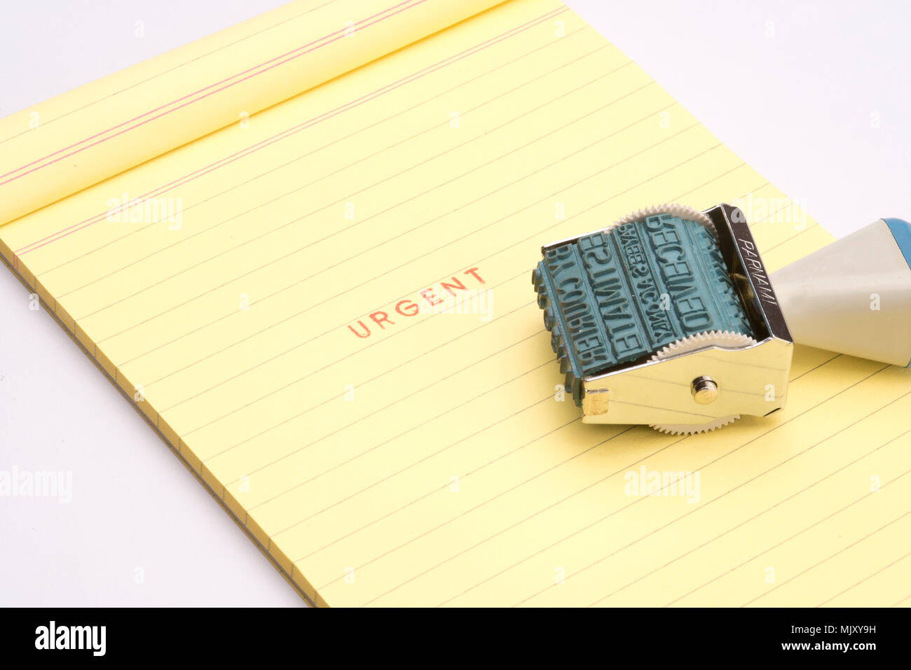 'Urgent' rubber stamp with yellow note pad - Stock Image