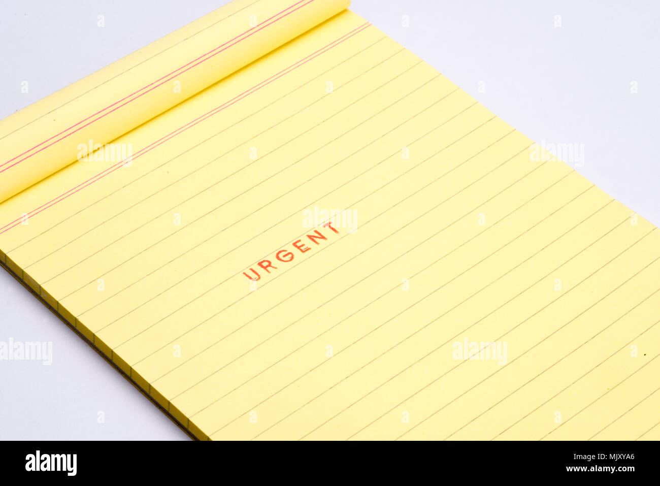 'URGENT' rubber stamp on yellow note pad. - Stock Image