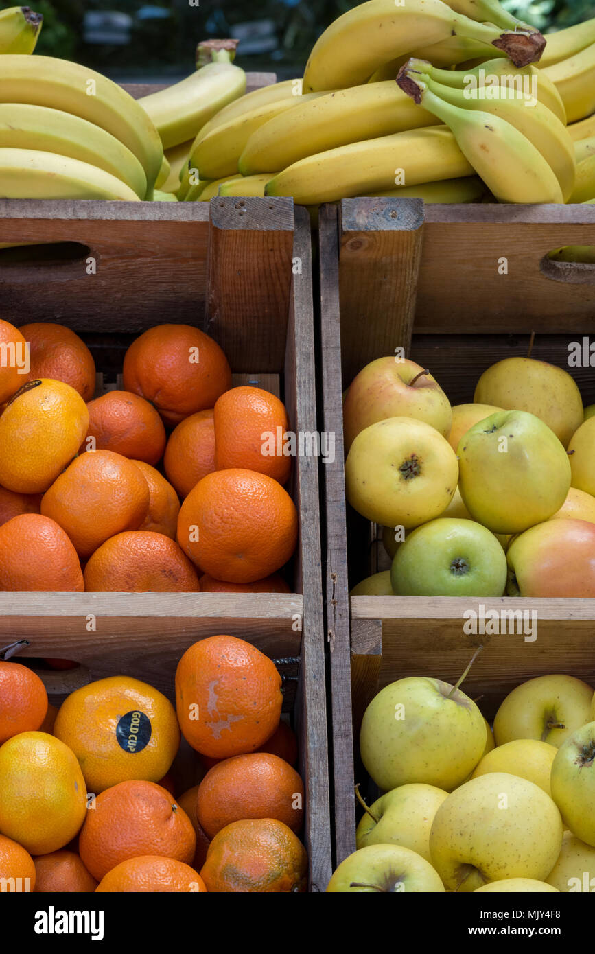 fresh apples, bananas and oranges fresh fruits on a market stall for sale on borough market in central London. - Stock Image