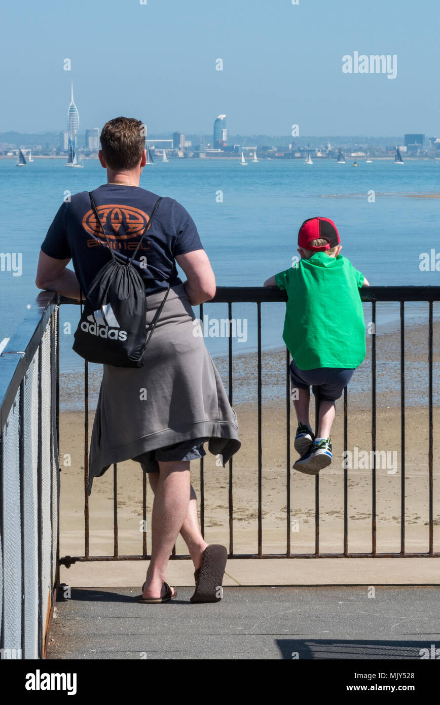 A father and son man and boy spending family time together looking out over the sea leaning on some railings. Families and togetherness dad and lad. - Stock Image