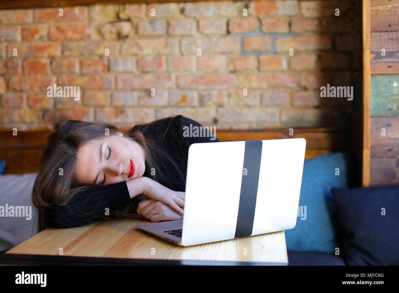 Exhausted pretty student sitting near modern laptop at cafe on sofa. - Stock Image