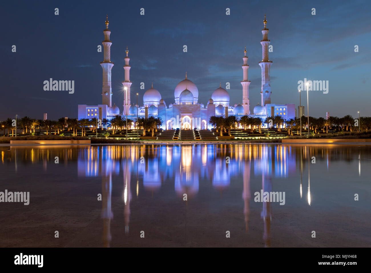 Sheikh Zayed Grand Mosque in Abu Dhabi, capital city of the United Arab Emirates. Mosque is built from Italian white marble. Reflection in lake - Stock Image