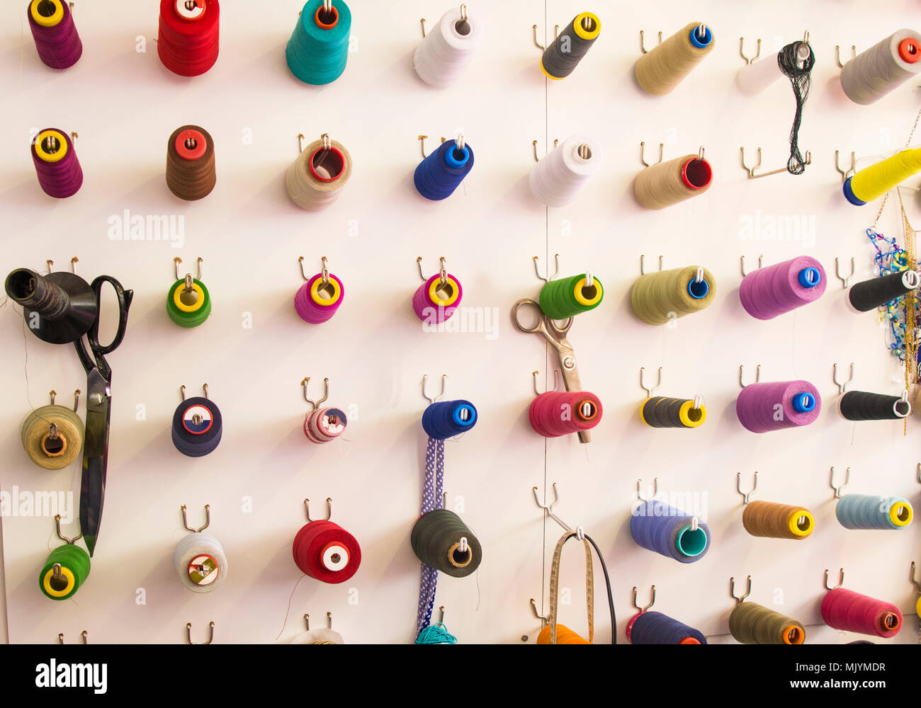 Multicolored coils and scissors on the wall. Workplace seamstresses - Stock Image
