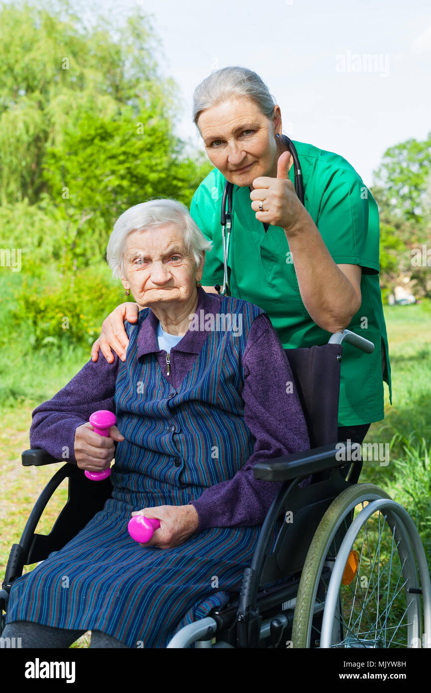 Senior woman in the park with cheerful middle aged caregiver - Stock Image