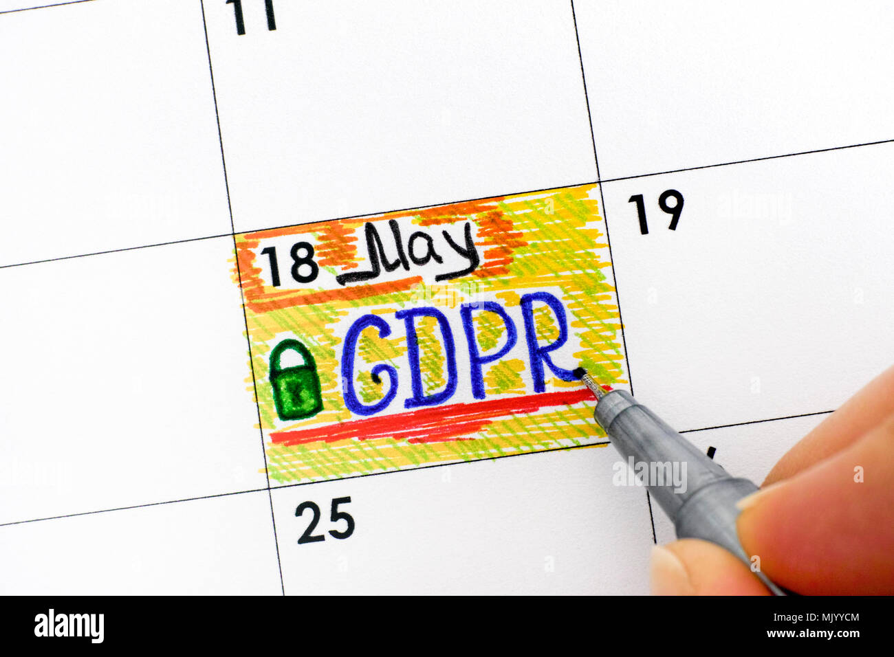 Woman fingers with pen writing reminder GDPR in calendar. Close-up. - Stock Image