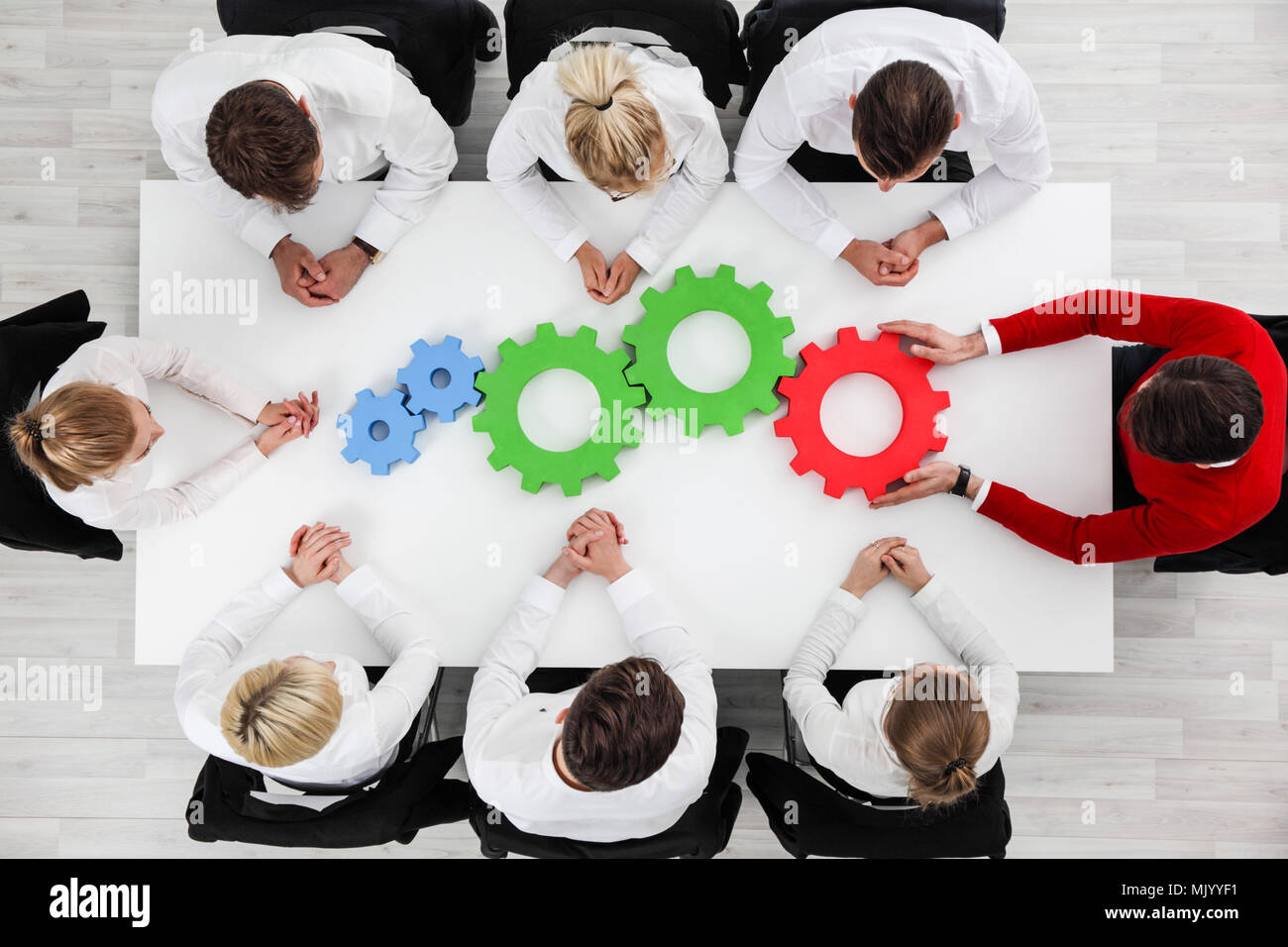 Business problem solution, mechanism of business, teamwork concept, business team sitting around white table with cogs - Stock Image
