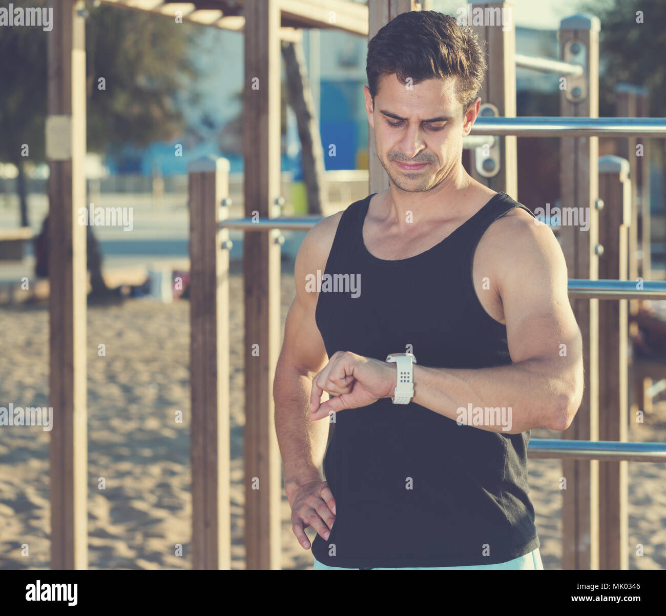 Physically fit man looking at smartwatch on sport ground on beach - Stock Image