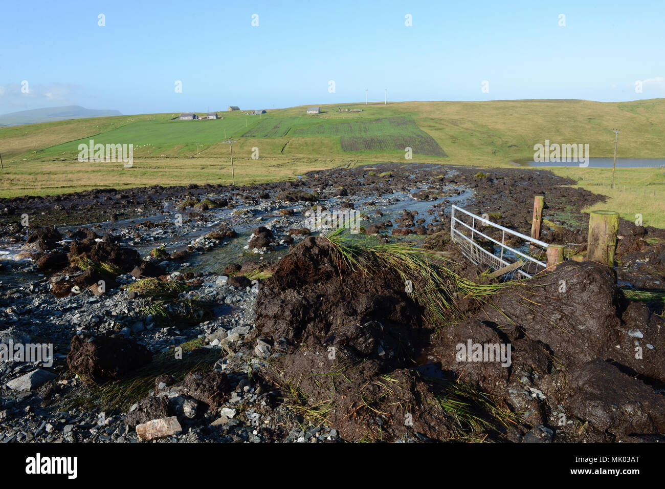 Peat landslide on the hills around a couple of house and settlements Stock Photo