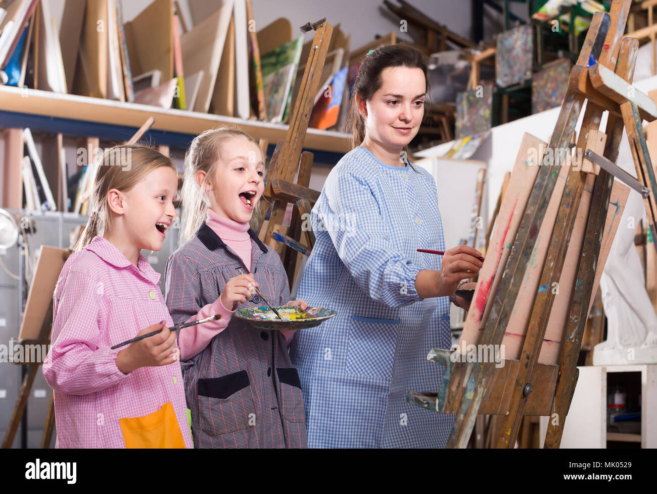 skillful young spanish woman teacher showing her skills during painting class at art studio - Stock Image