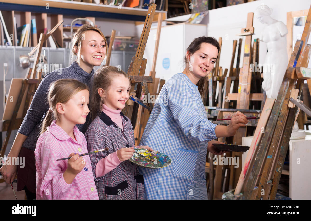 skillful young germany woman teacher showing her skills during painting class at art studio - Stock Image