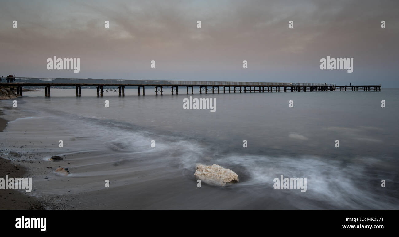 Seascape with jetty during a dramatic cloudy sunset at Polis