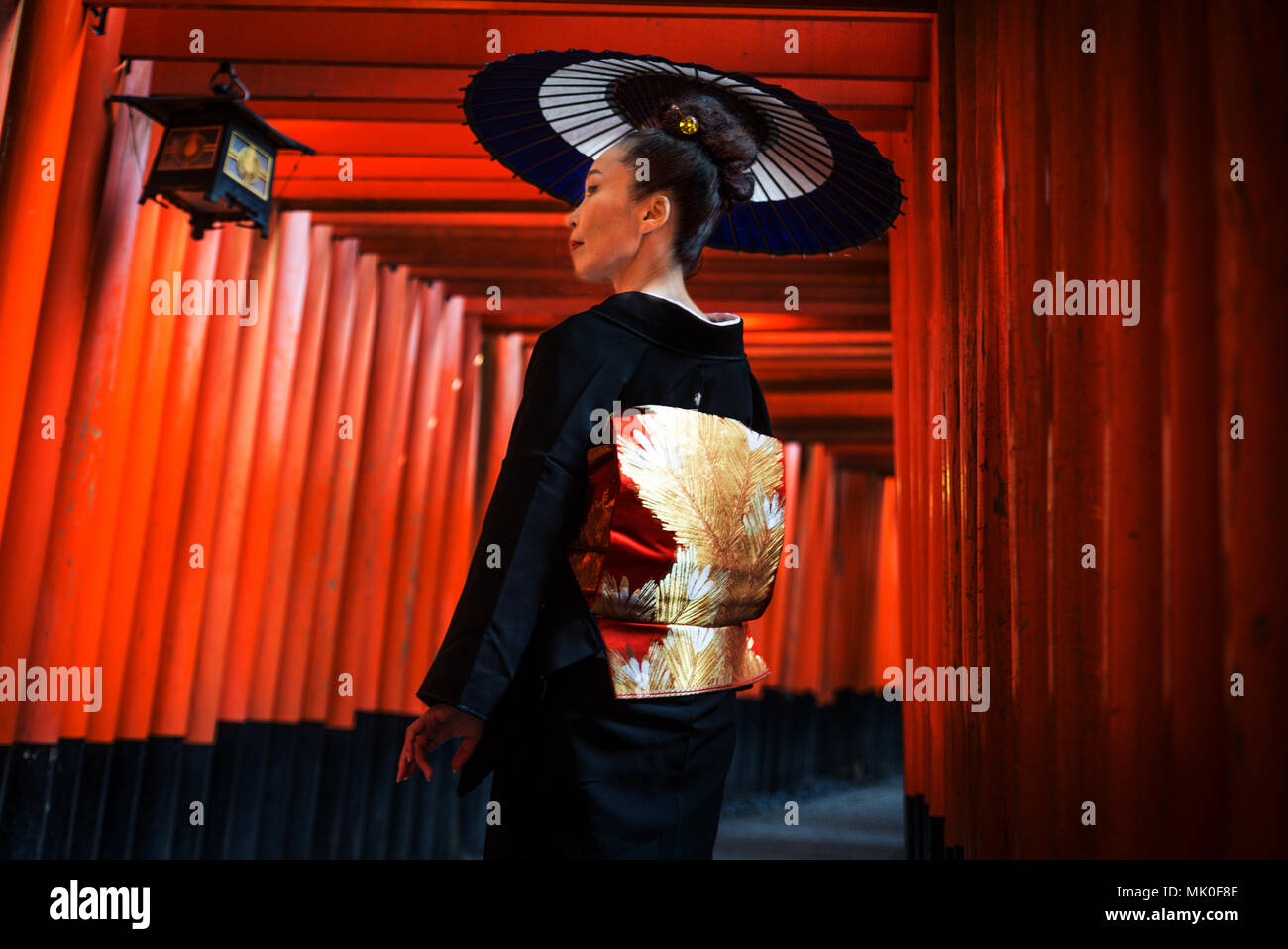 Asian woman in traditional japanese kimonos at Fushimi Inari Shrine in Kyoto, Japan - Stock Image