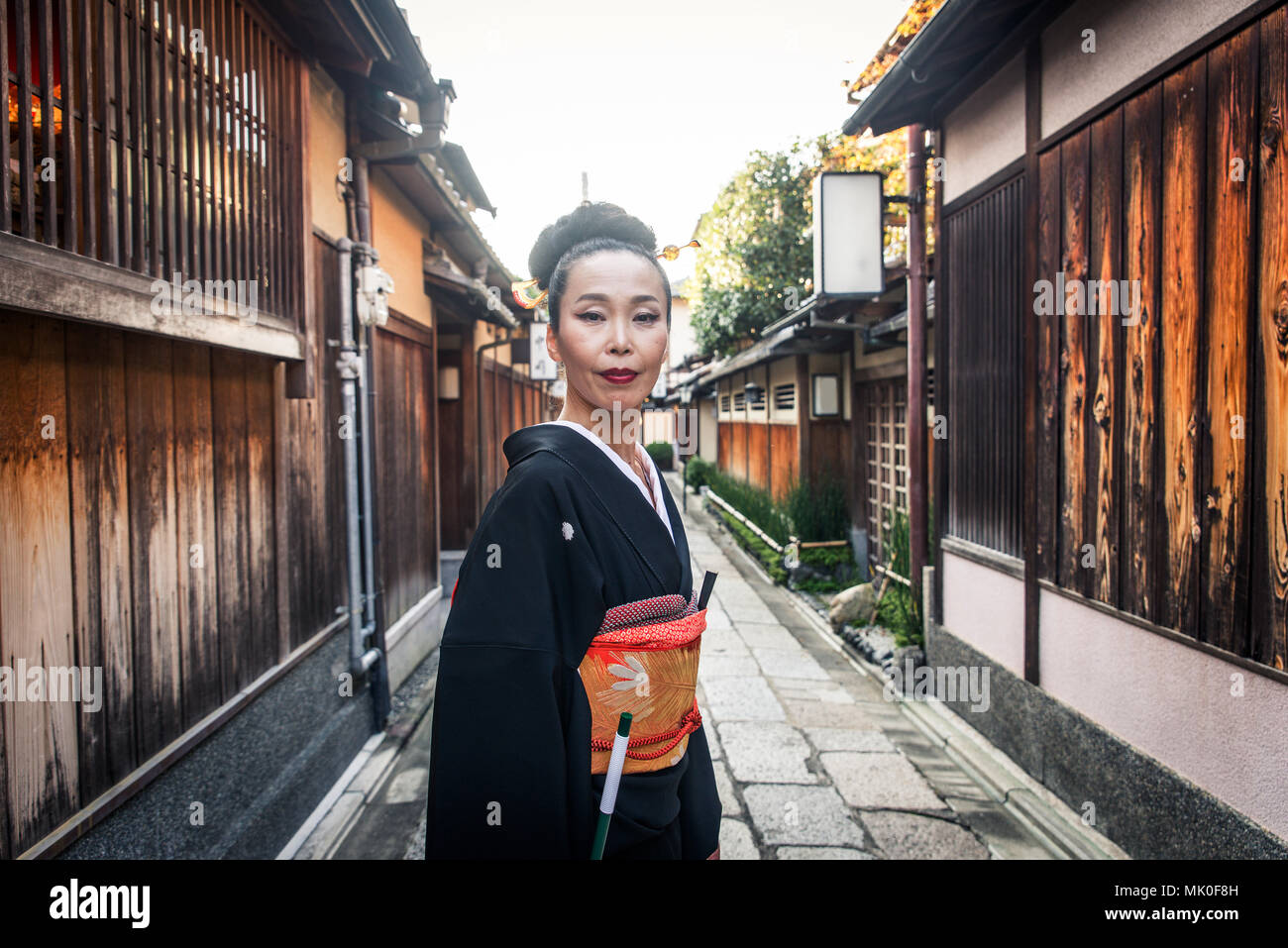 Japanese woman wearing traditional dress and walking outdoors - Stock Image