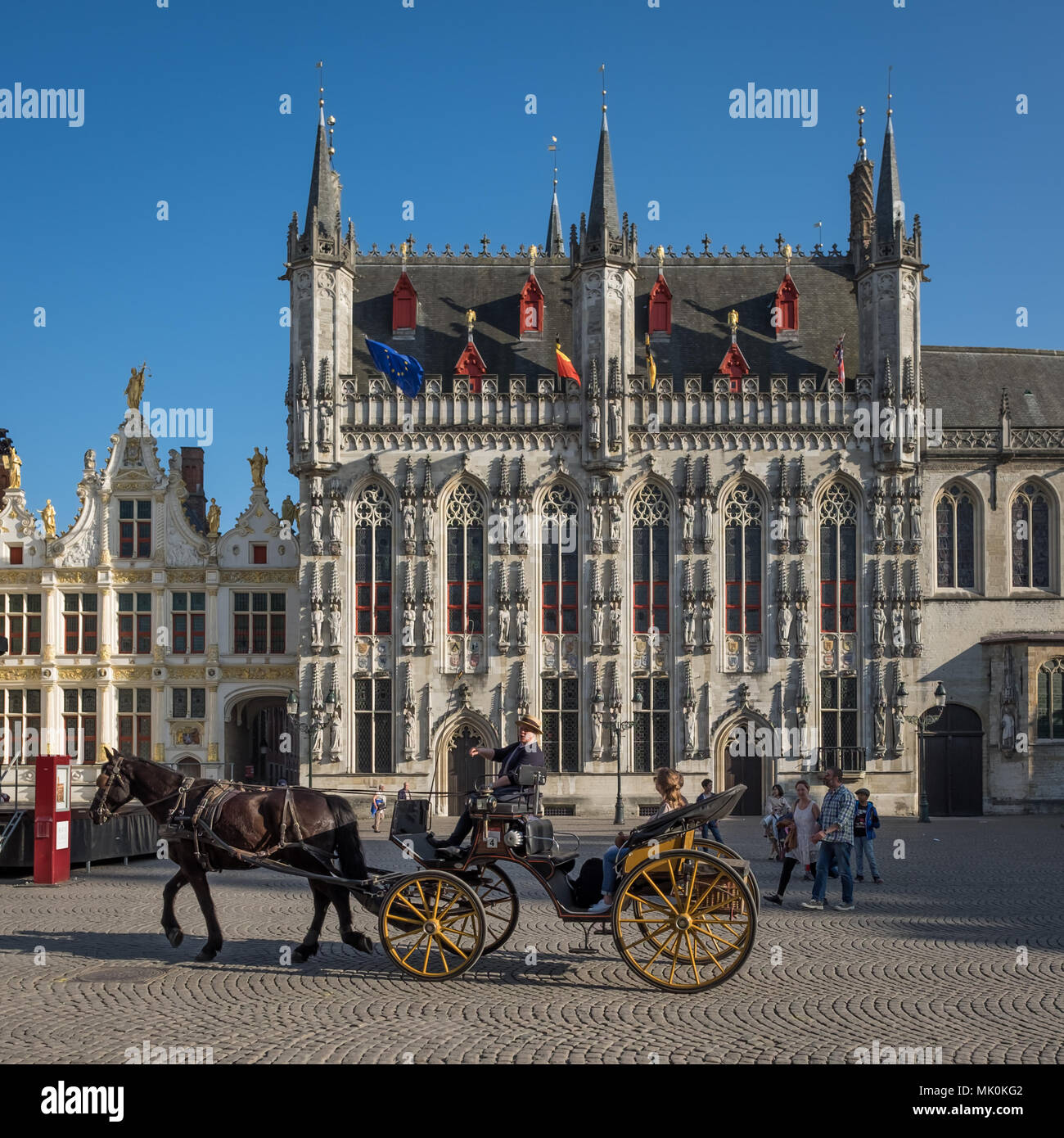 Tour guide and tourists on cart and horse on 'Burg' square in Brugge, Belgium. - Stock Image
