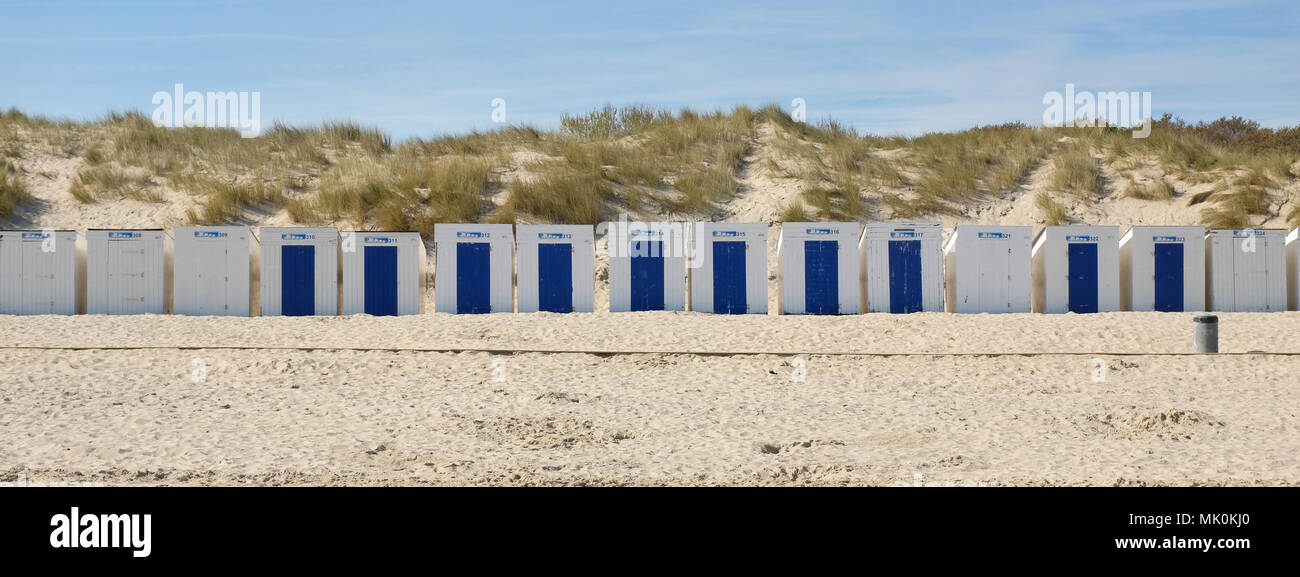 Row of blue and white beach houses on one of the many beaches in Zeeland, the Netherlands. - Stock Image