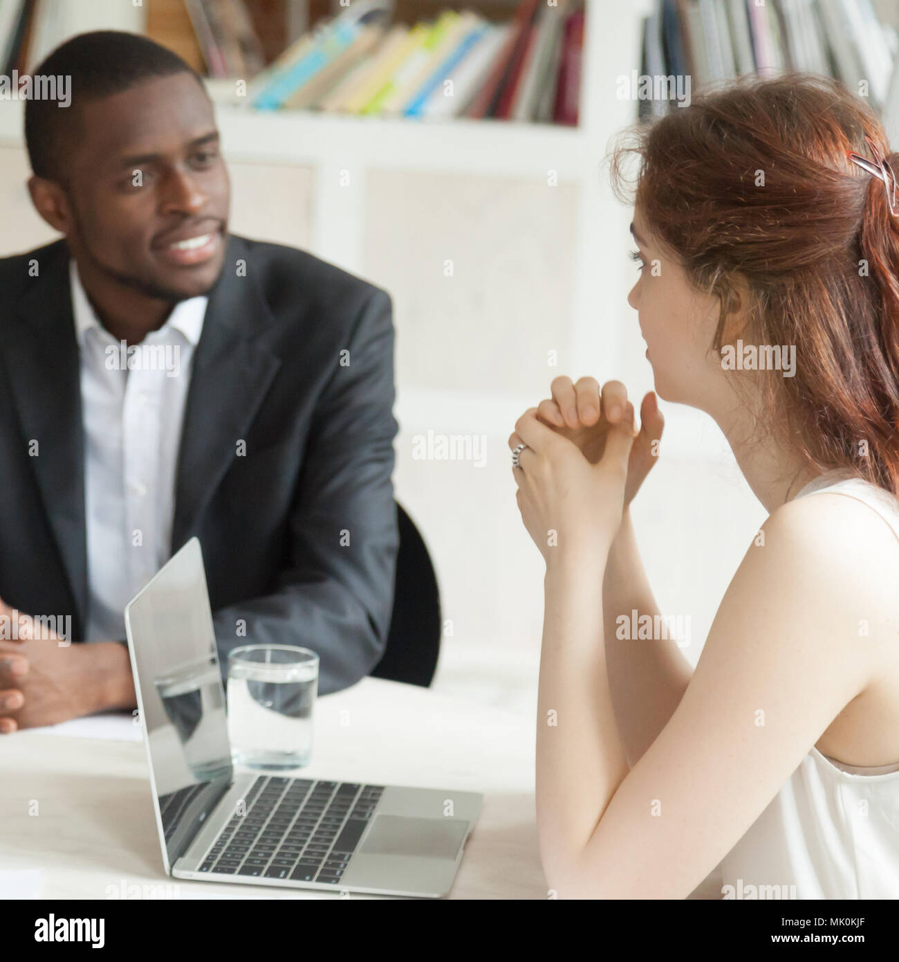 Male african american and female caucasian negotiating at briefi - Stock Image