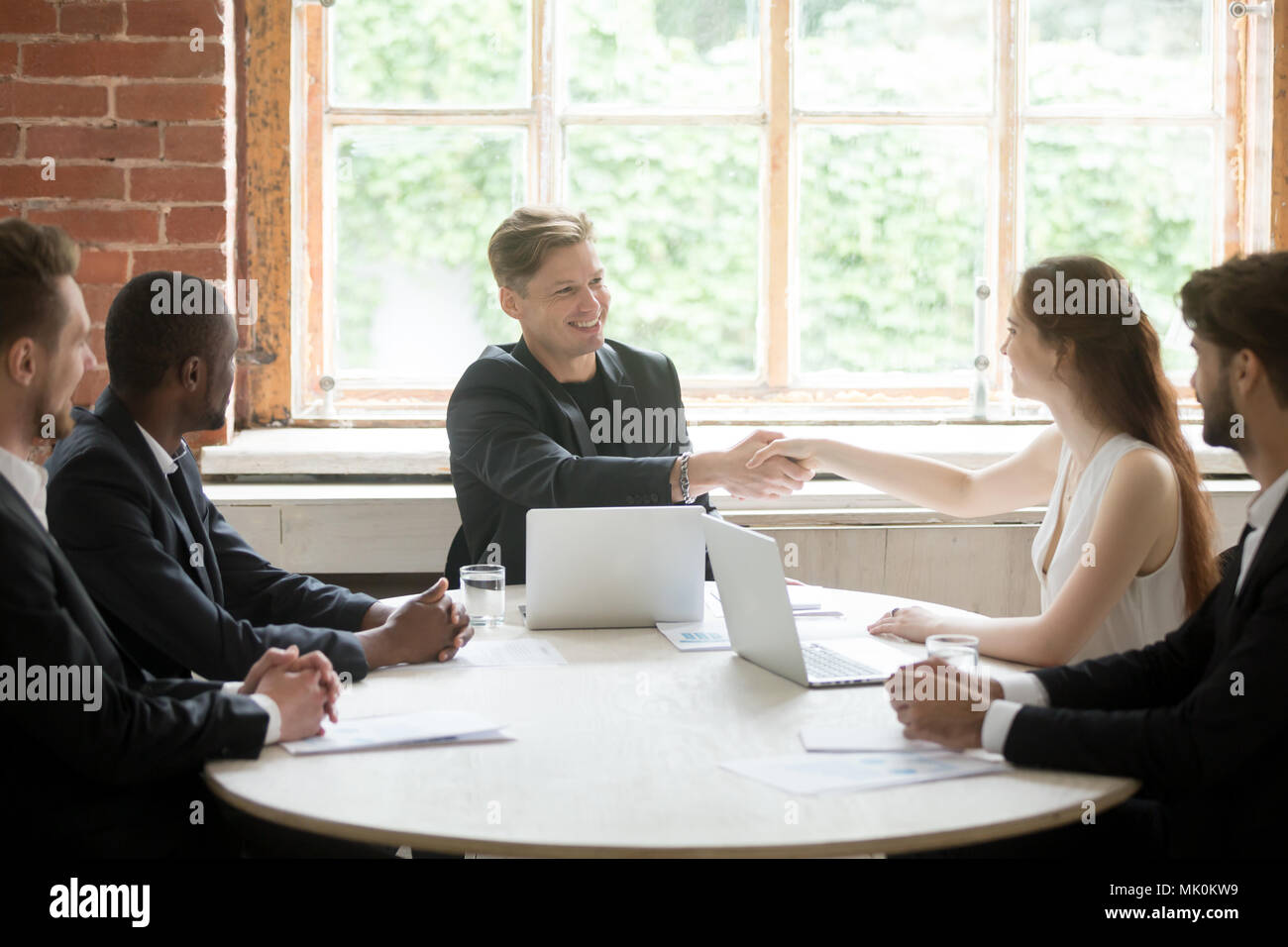 Smiling CEO greeting female business colleague by handshake - Stock Image