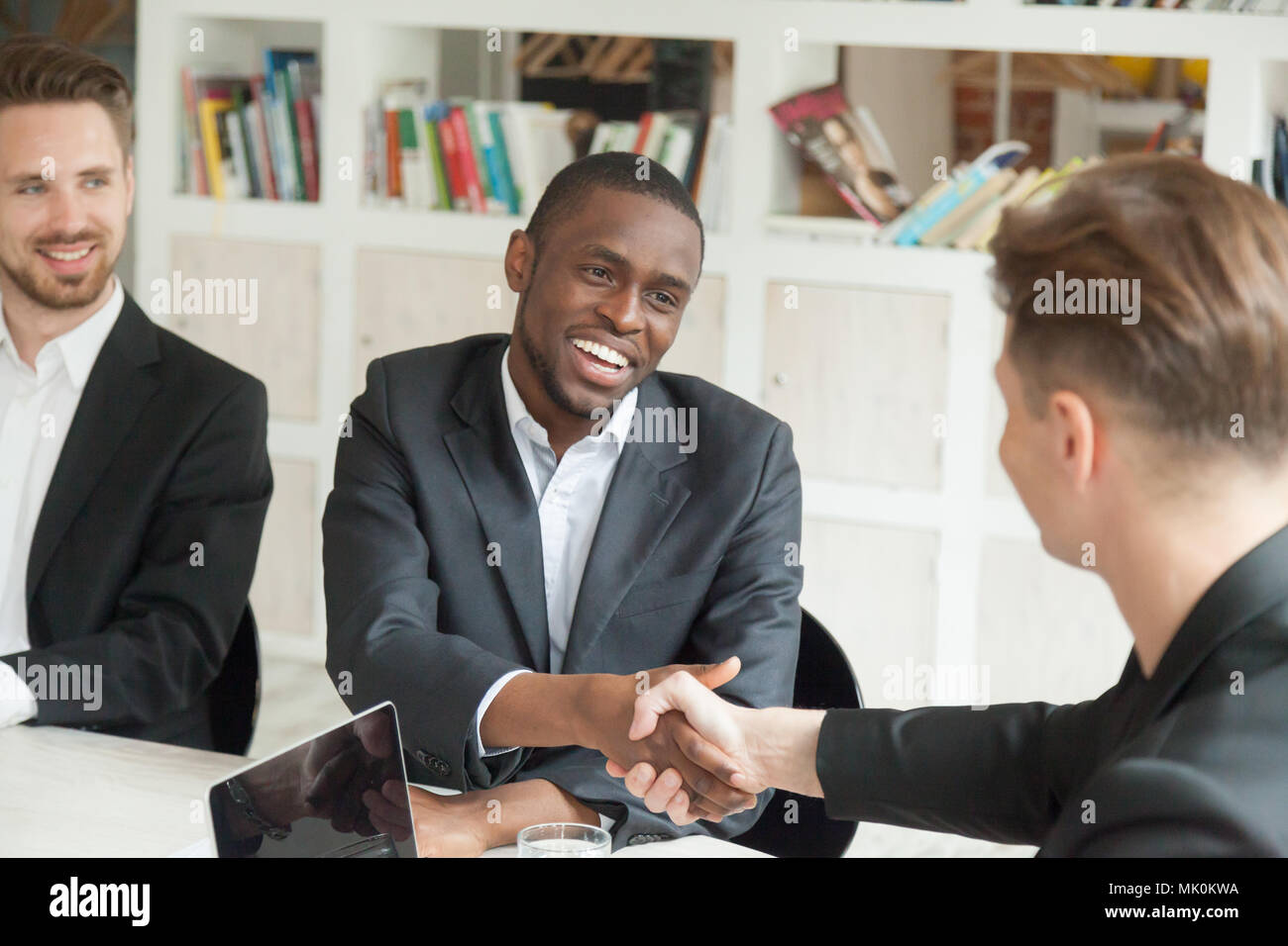 Team leader greeting black colleague with promotion - Stock Image