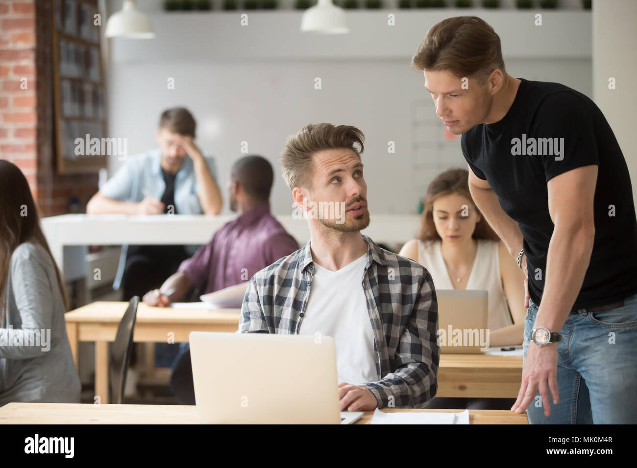 Male intern asking for help from supervisor - Stock Image