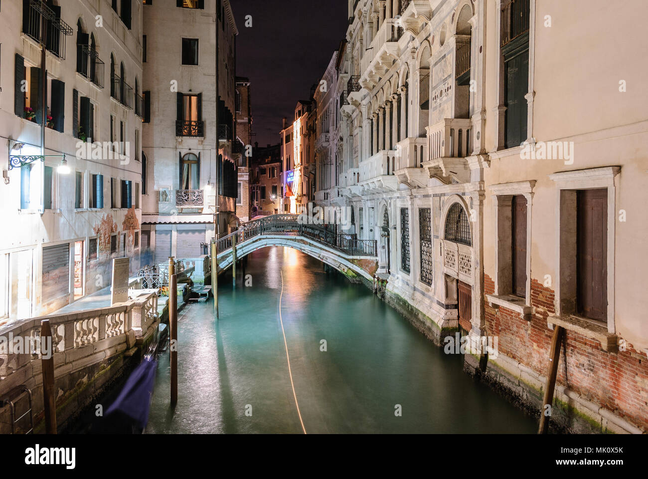 Night view of a typical canal in Venice with the light trail of a boat - Stock Image