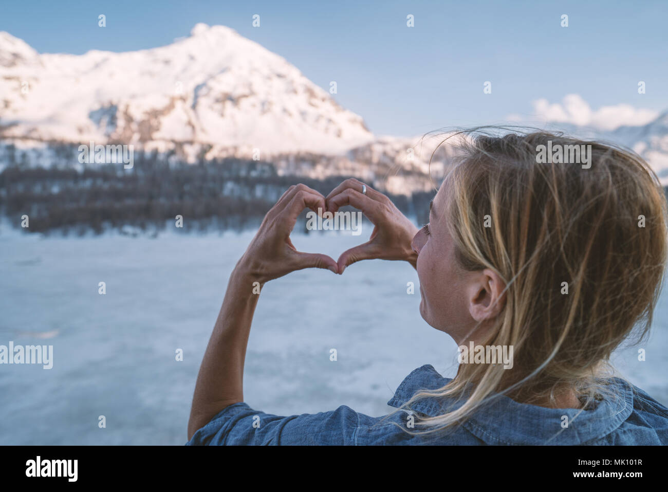 Young woman making a heart shape finger frame over frozen lake and snowcapped mountains. People love nature environment concept. Shot in Switzerland Stock Photo