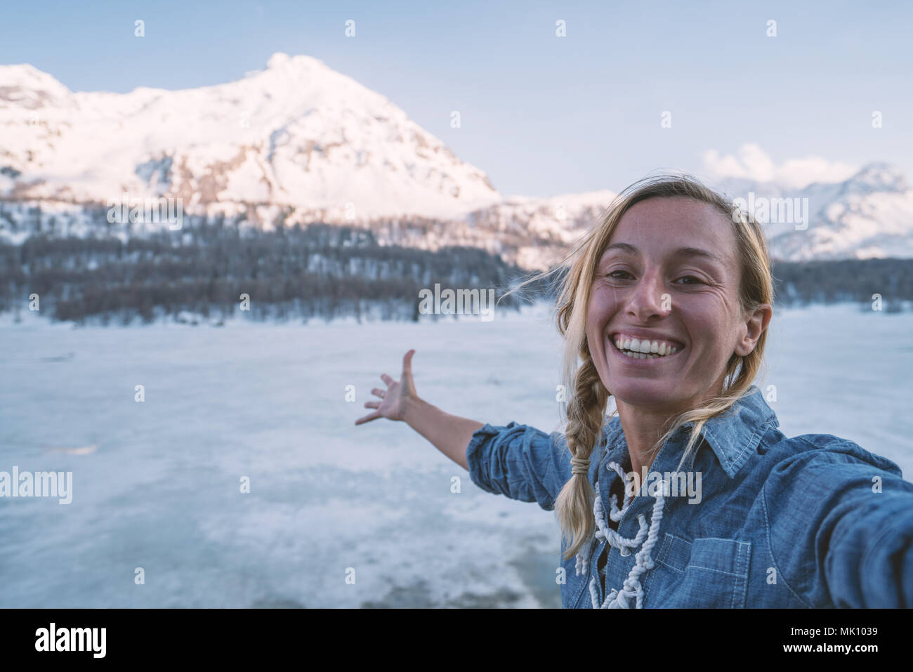 Young woman taking a selfie portrait near a frozen lake with snowcapped mountains on the background at sunset. People travel fun concept, Switzerland. Stock Photo