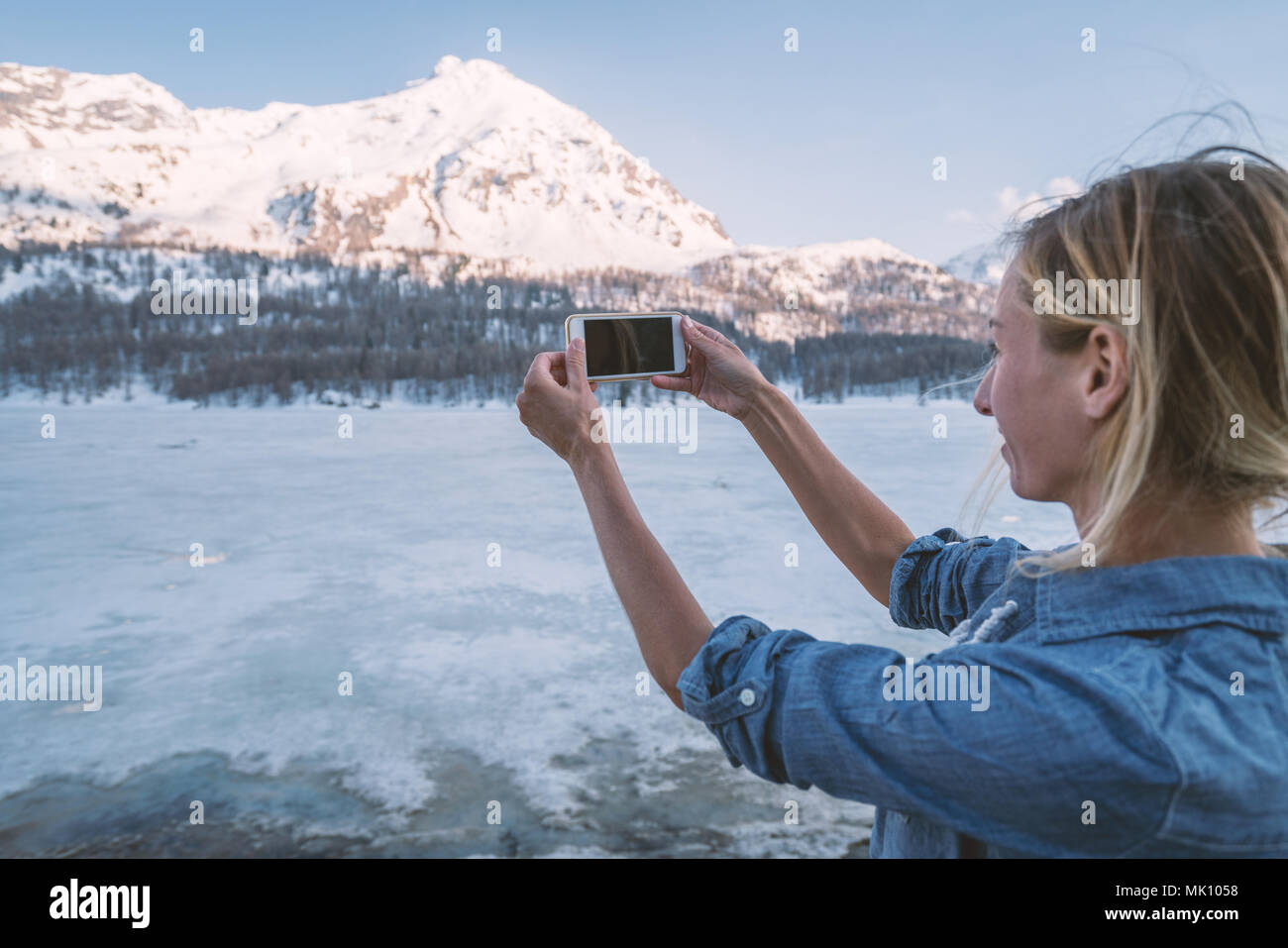 Young woman taking a mobile phone picture of stunning mountain landscape at sunset in Switzerland. People travel technology concept Stock Photo