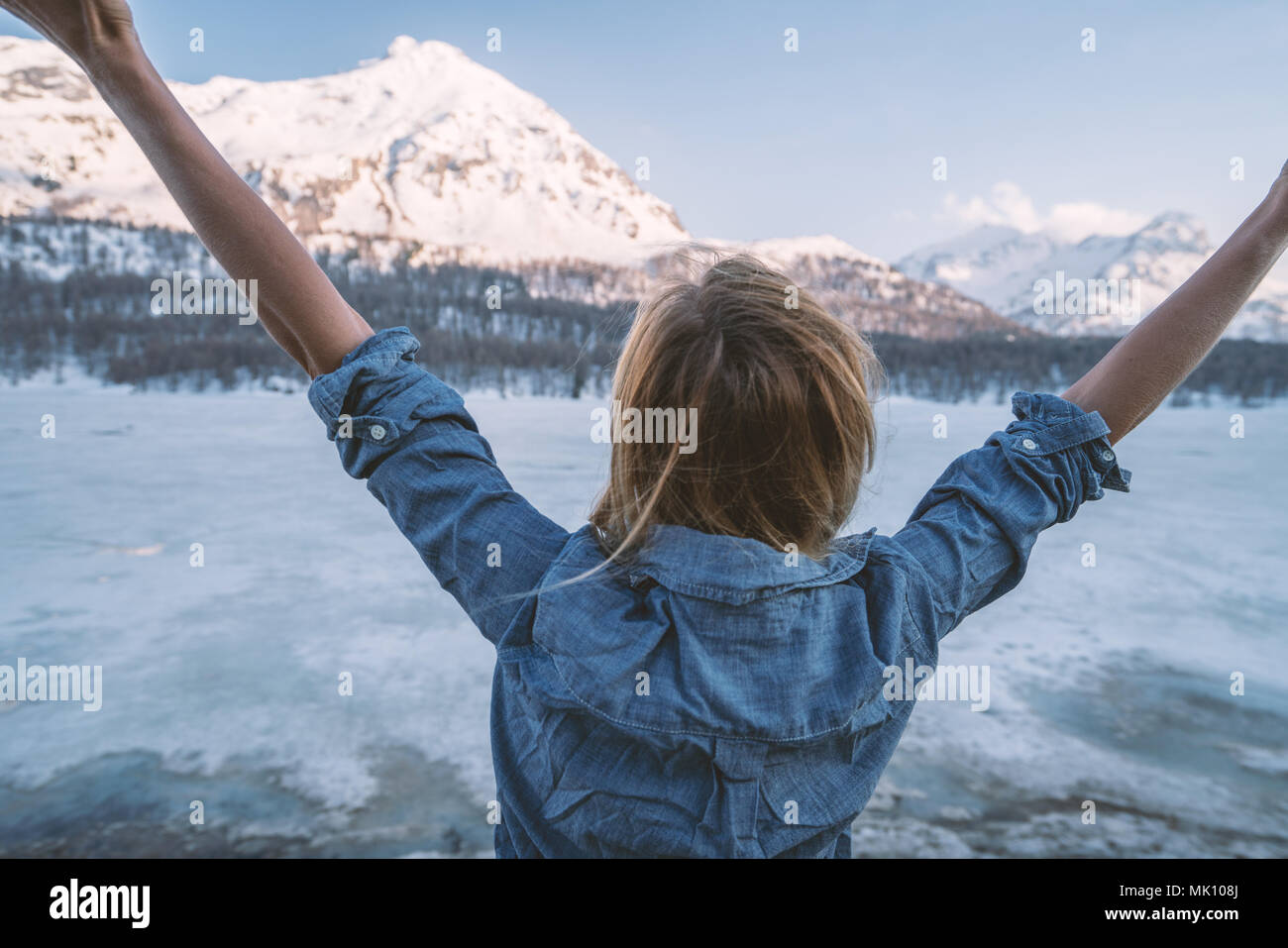 Young woman arms outstretched in nature, mountain landscape in Switzerland. People travel wellbeing freedom concept Stock Photo