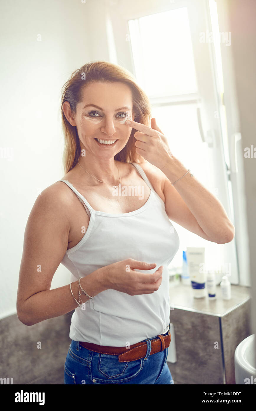 Beautiful blond woman in blue jeans and white shirt standing in home bathroom and applying face cream under her eyes, looking at camera and smiling - Stock Image