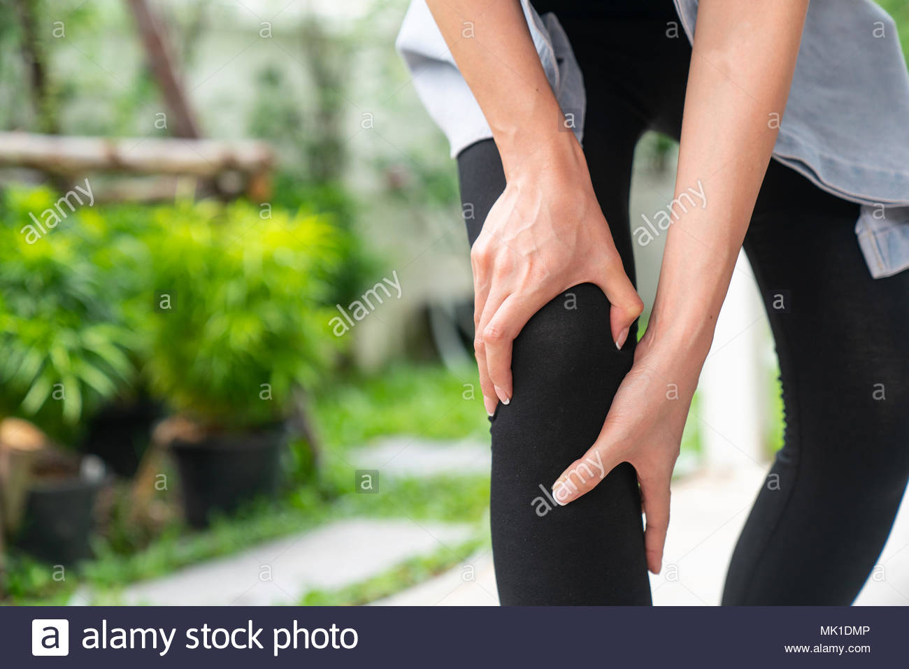 Young woman suffering from pain in knee, close up - Stock Image