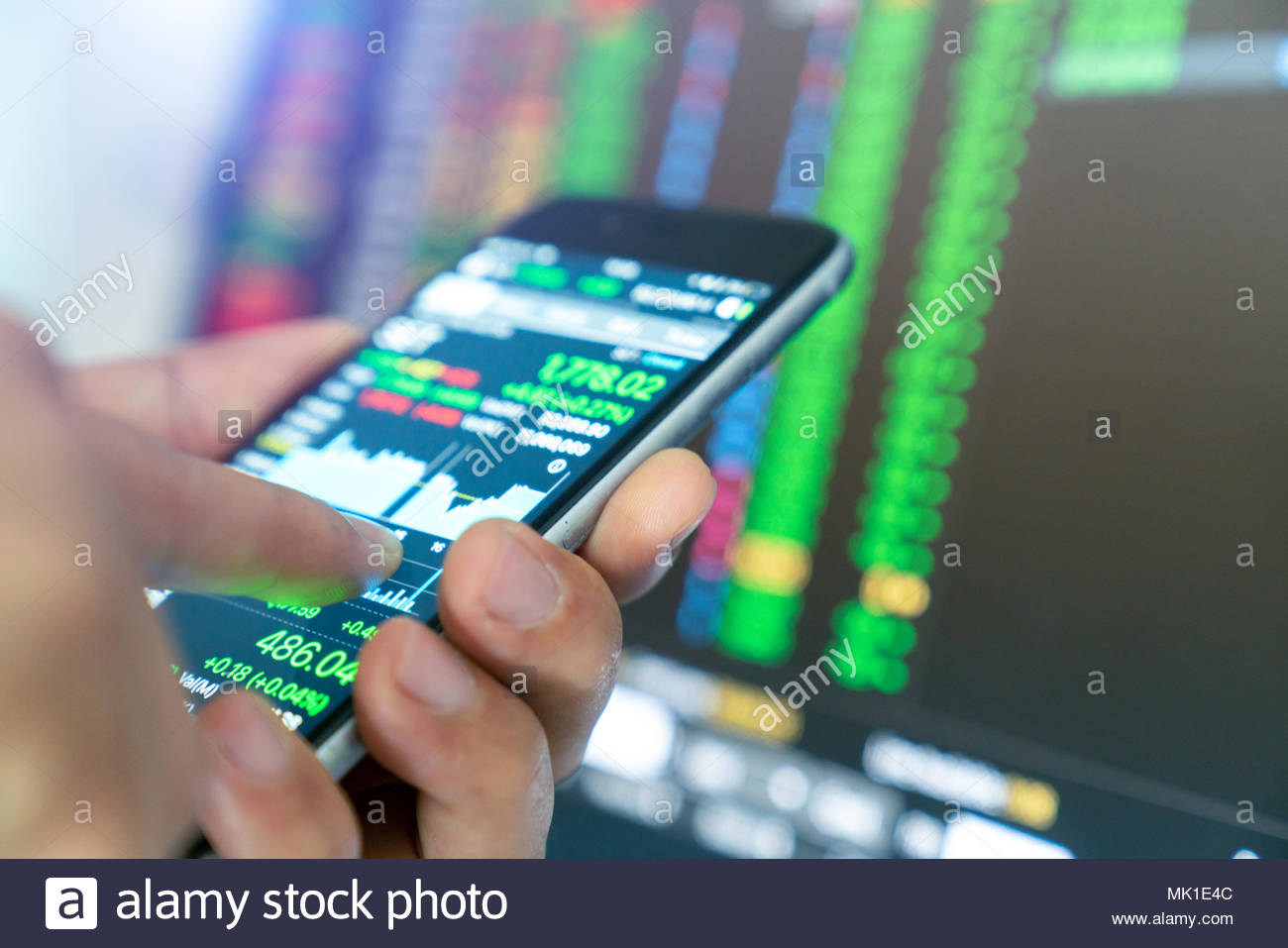 businessman using a mobile phone to check stock market data. - Stock Image
