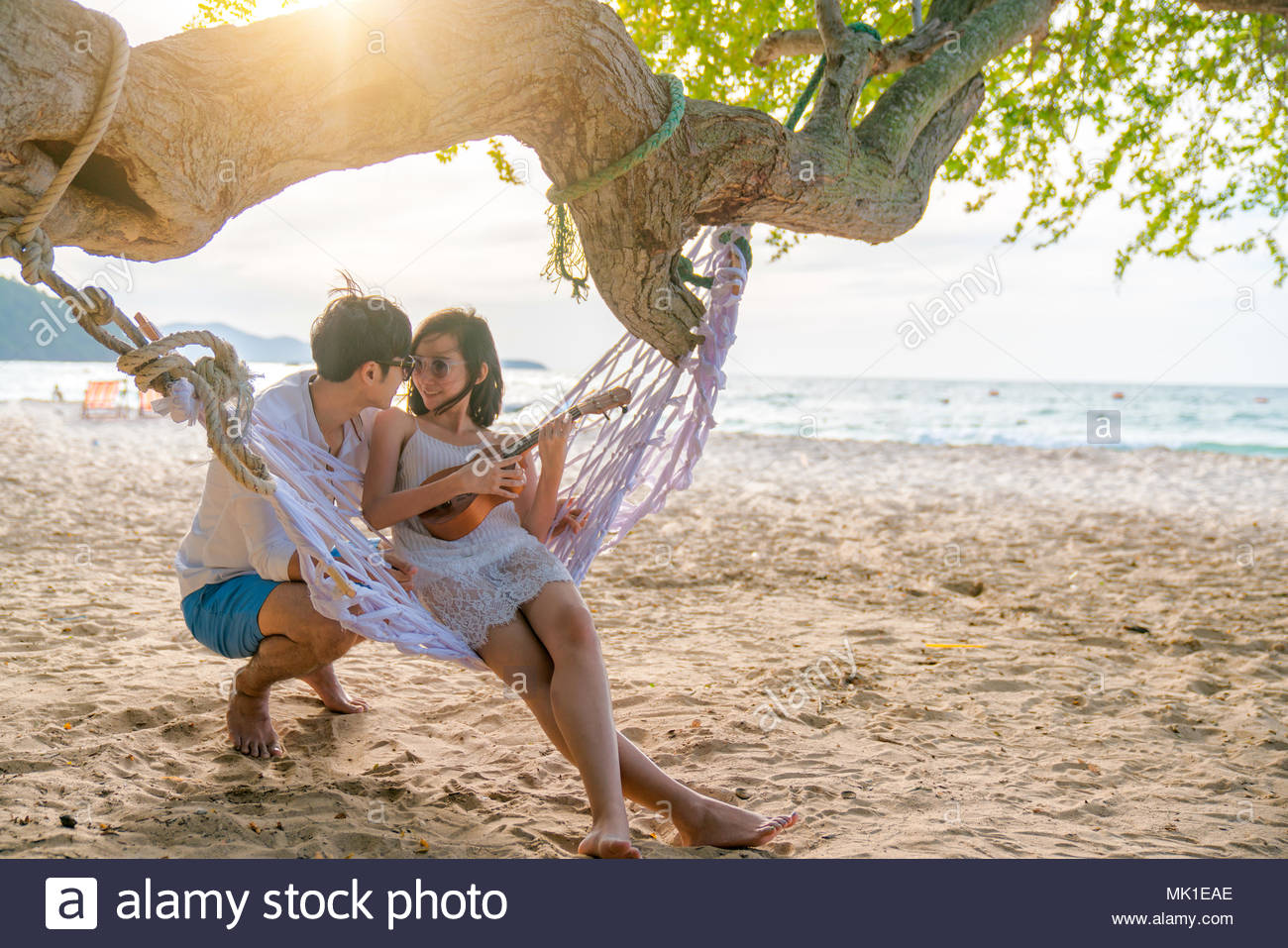 Romantic couple is sitting and kissing on sea beach on rope swing . Family vacation on honeymoon. Love and relationship - Stock Image