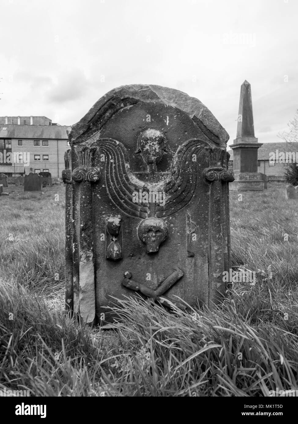 Glasgow scotland april 23rd 2018 a black and white photograph of an angel a skull and bone cross on a gravestone at the govan old parish church