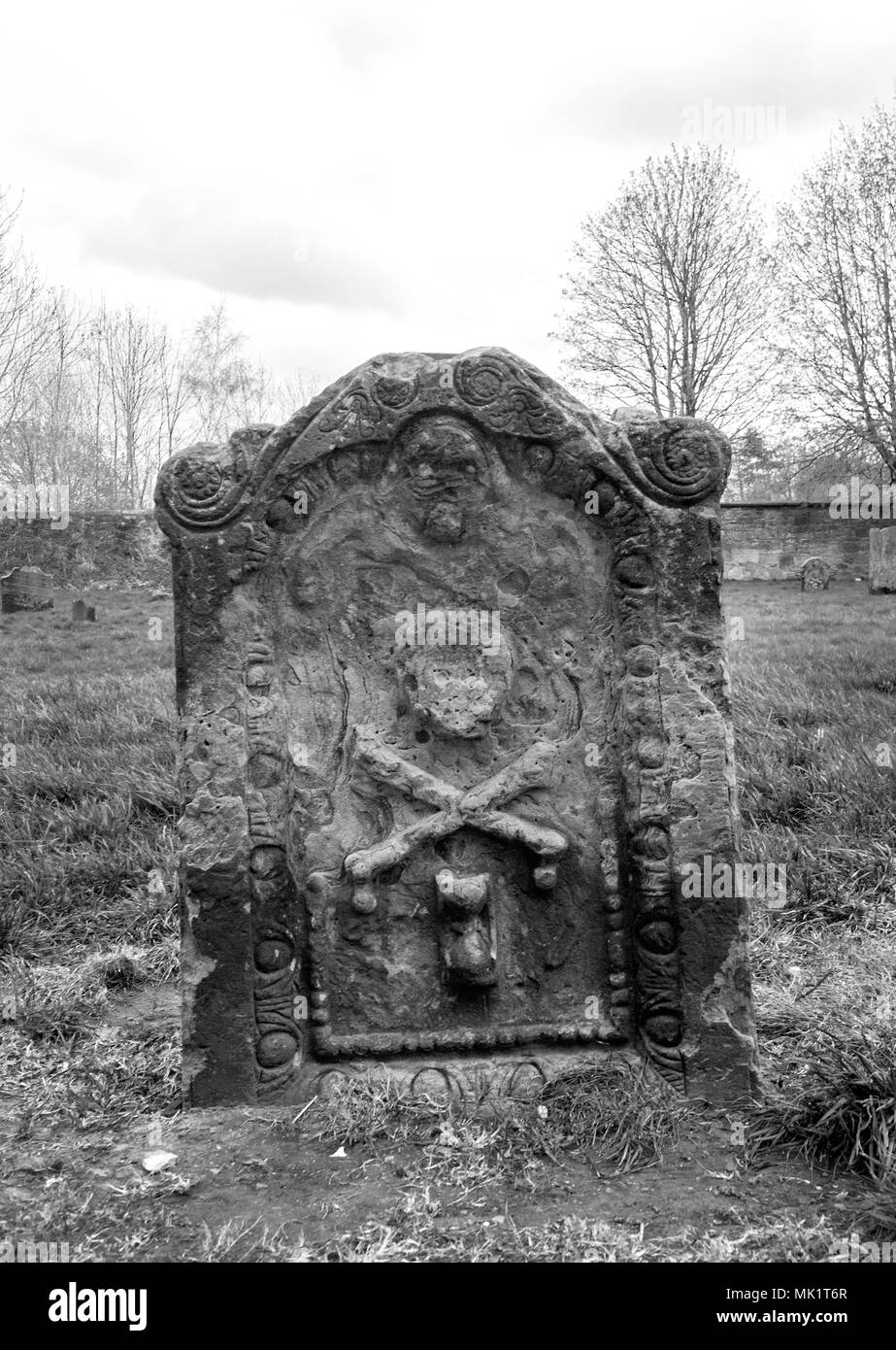 Glasgow scotland april 23rd 2018 a black and white photograph of a skull and bone cross on a gravestone at the govan old parish church