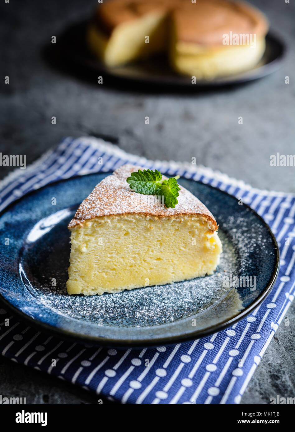 A slice of delicious Japanese cheesecake with powdered sugar icing - Stock Image