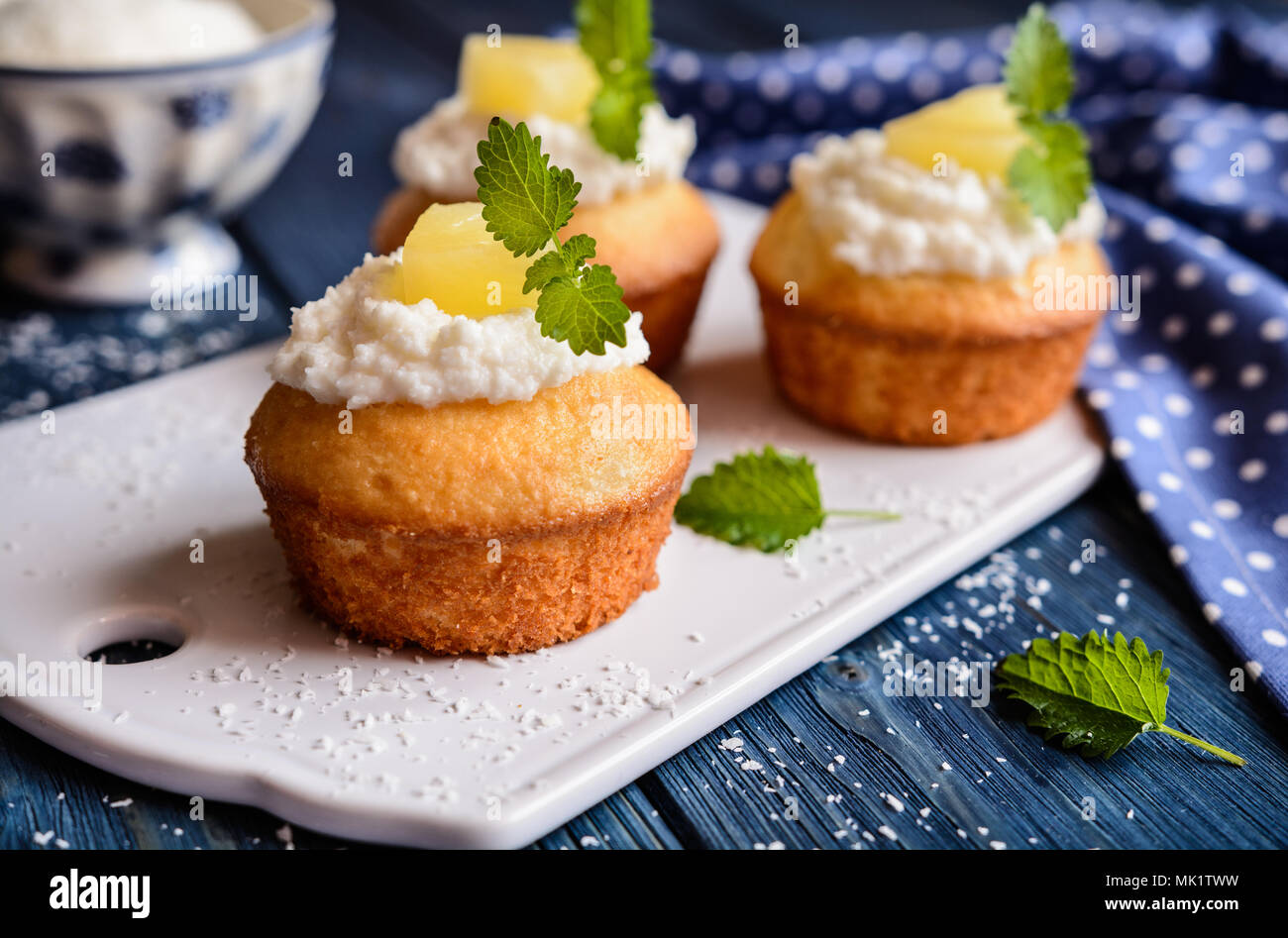 Coconut and pineapple muffins with yoghurt topping - Stock Image