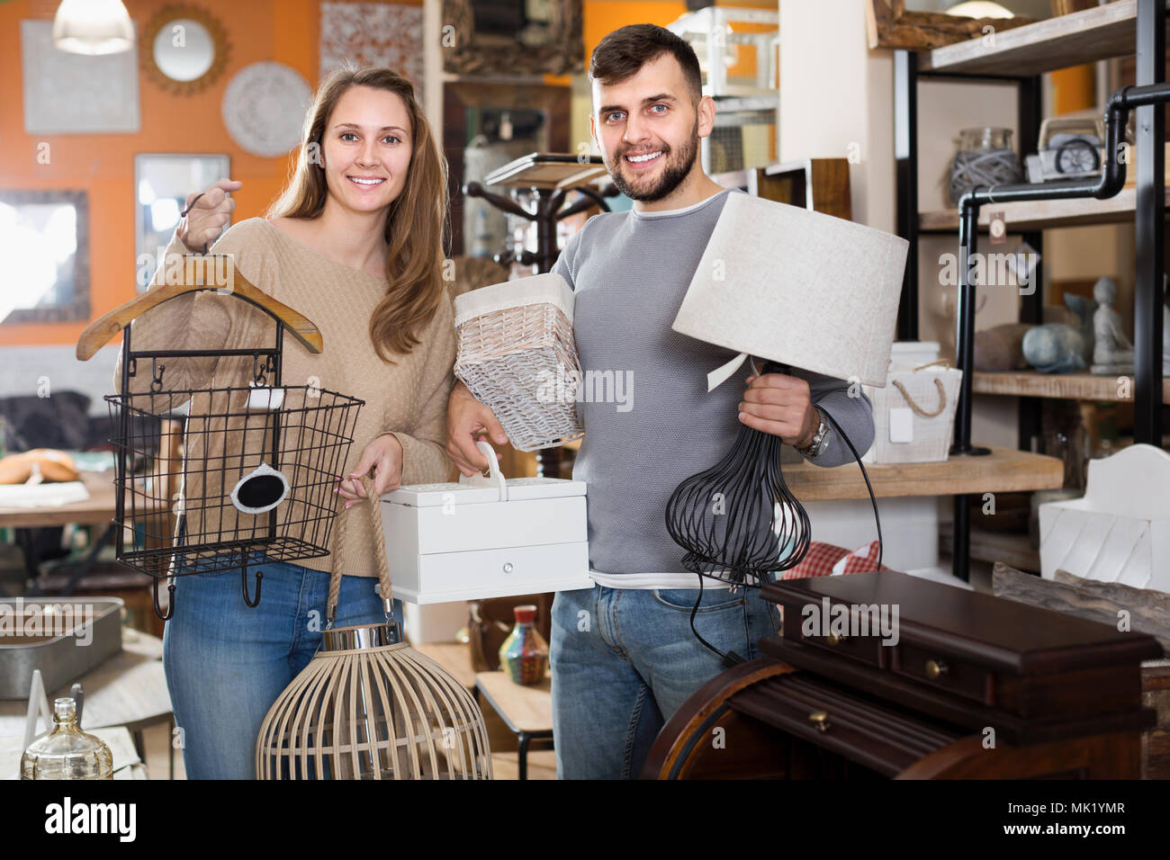 Satisfied couple demonstrating their buies in shop of secondhand furniture - Stock Image