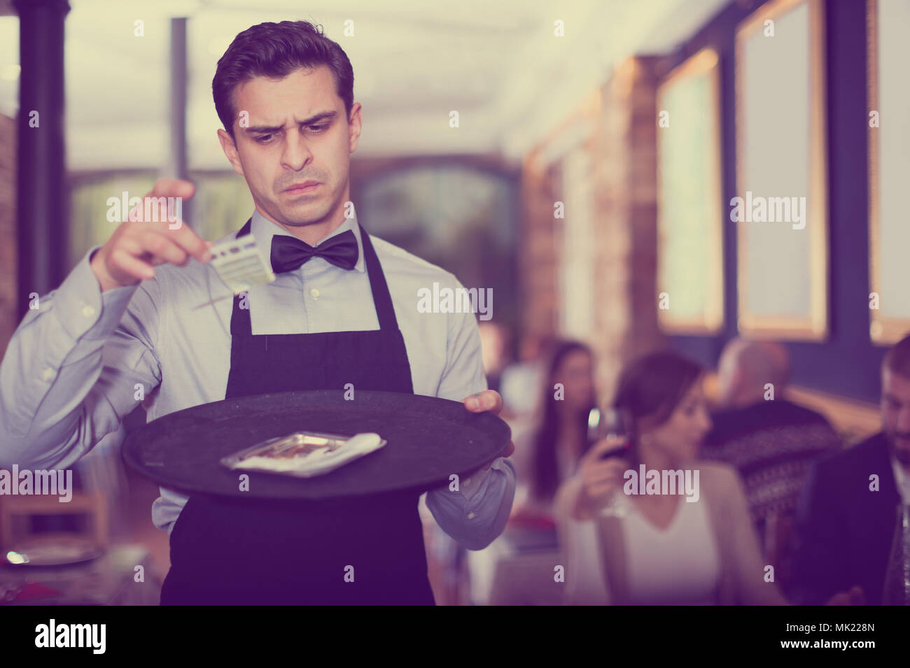 frustrated male waiter looking at a tip on a tray in a cafe - Stock Image