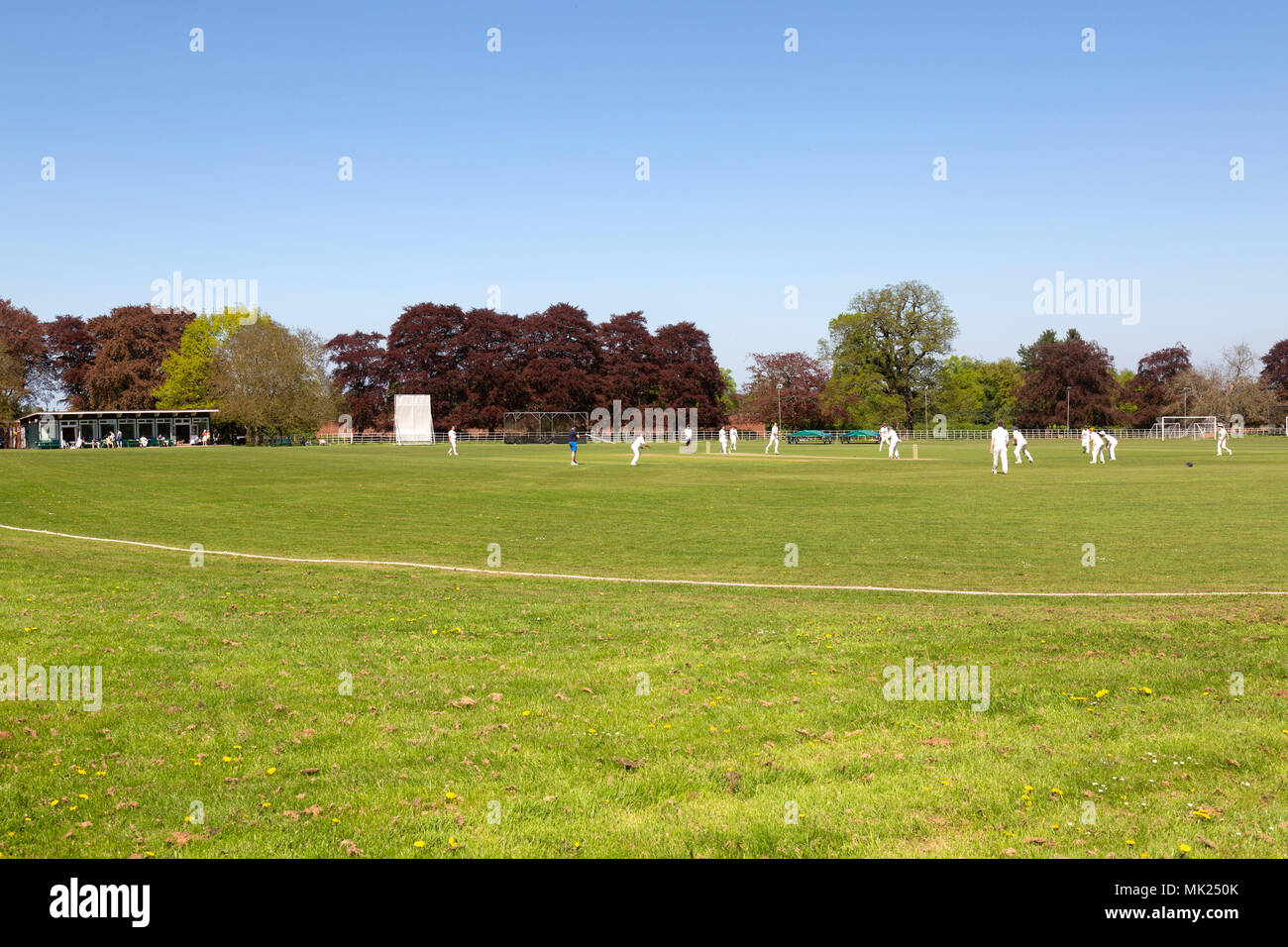 A cricket match on an English cricket field in Enville, Staffordshire, in the summer, showing cricket pavilion on the left. - Stock Image