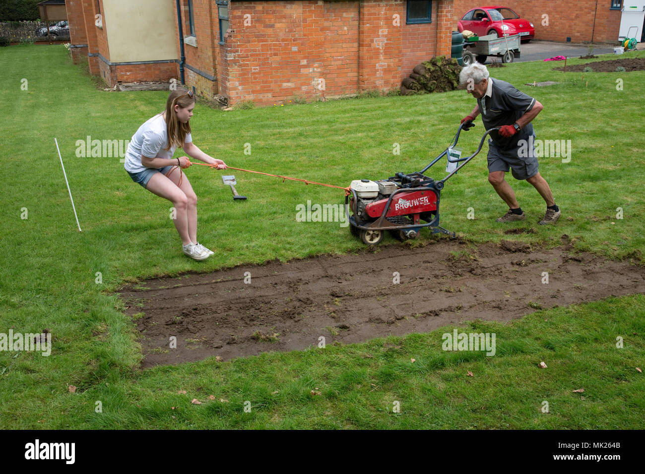 Man and teenage girl turf cutting Three Bees Community Garden April 2018 Mickleton Cotswolds UK - Stock Image