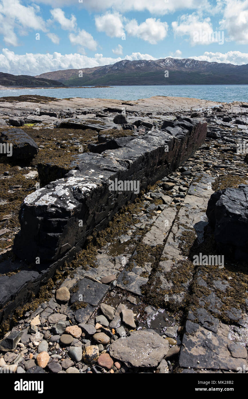 Fine straight vertical intrusive volcanic mafic basalt dyke on Boreraig beach, Isle of Skye, Scotland, UK. (Also see images MK28B3, 4 & 5) - Stock Image