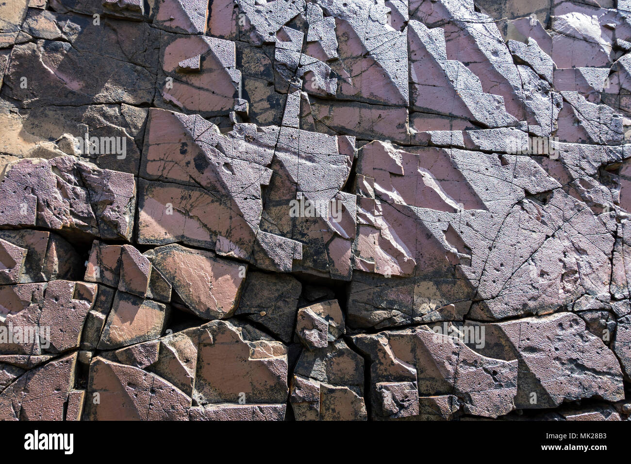 Closeup of geometric fractured rock surface of vertical volcanic dyke (see image MK28B2) on Boreraig Beach, Isle of Skye, Scotland, UK - Stock Image