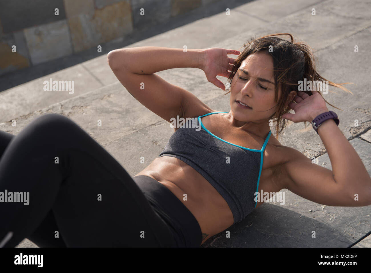 Healthy looking woman in fitness clothing training really hard with her legs bent and her arms behind her head - Stock Image