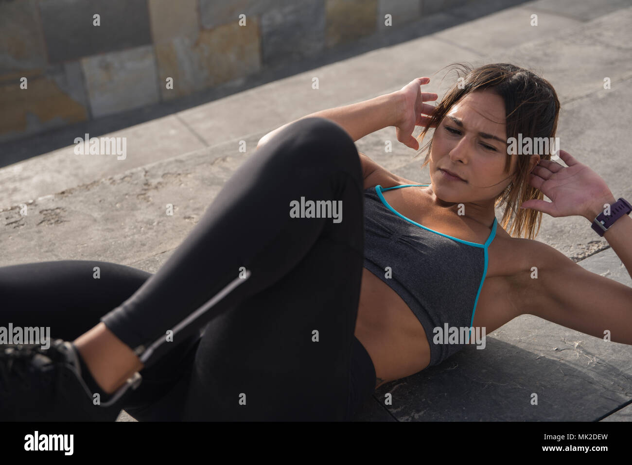 Young fit brunette exercising outside in the sun in black tights, a grey sports vest and black sneakers - Stock Image